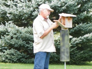 Ray Pinter inspects a box.  The post shield keeps predators away from the nest.